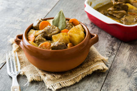 Beef stewed with potatoes, carrots and spices in ceramic bowl on wooden table Stock Photo