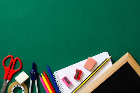 School supplies on green background. Back to school concept. Copyspace.