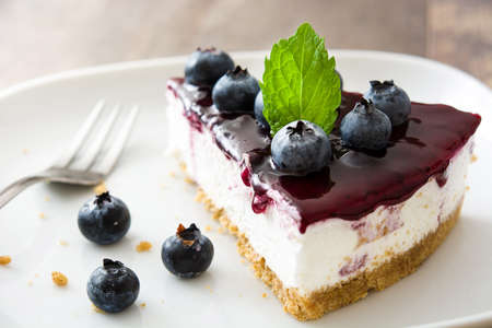 Piece of blueberry cheesecake on wooden table Zdjęcie Seryjne