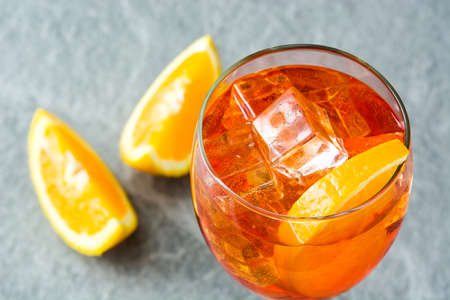 Aperol spritz cocktail in glass on gray stone Stock Photo