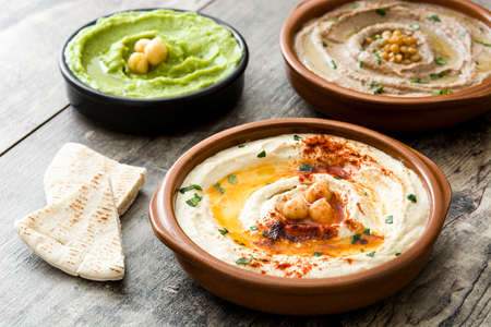 Diverse ciotole di hummus. Hummus di ceci, hummus avocado e lenticchie hummus sul tavolo di legno Archivio Fotografico - 83495858