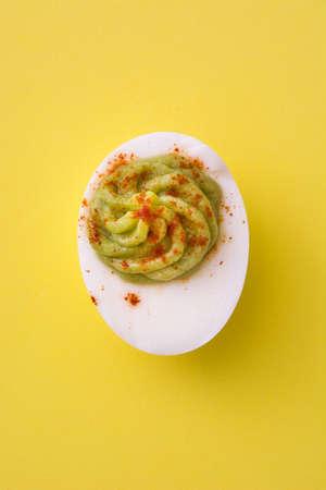 黄色の背景にグアカモーレとパプリカのぬいぐるみ卵
