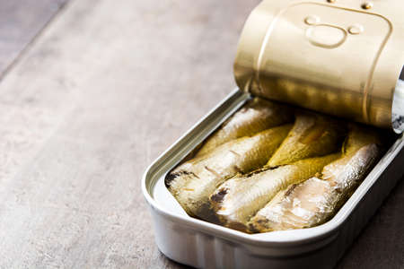 Cans of sardines on wooden table.Copyspace