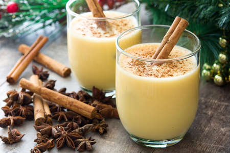 Homemade eggnog with cinnamon on wooden table. Typical Christmas dessert.