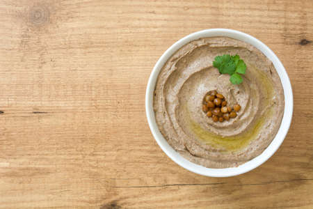 Lentil hummus in bowl on wood