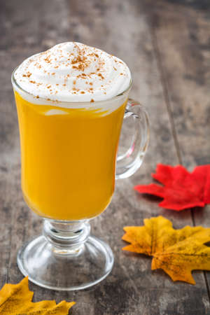 Pumpkin spiced latte on wooden table Stock Photo