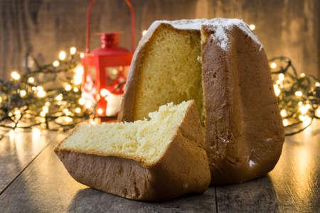Pandoro Christmas cake with sugar and christmas light on wooden table