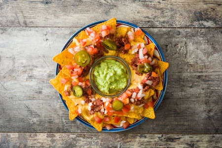Mexican nachos with beef, guacamole, cheese sauce, peppers, tomato and onion in plate on wooden table. Top view 写真素材