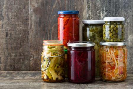 木製のテーブルの上の瓶に発酵保存野菜。コピースペース
