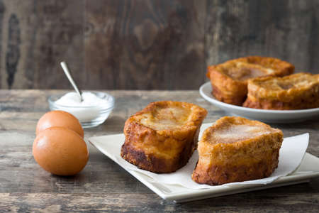Traditional homemade Spanish torrijas on wooden background. Easter dessert
