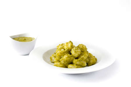 Gnocchi with pesto sauce in plate isolated on white background