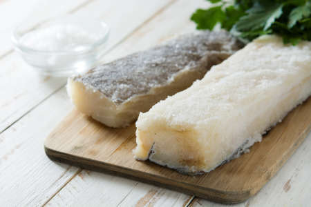 Salted dried cod on white wooden table. Typical Easter food Stock Photo