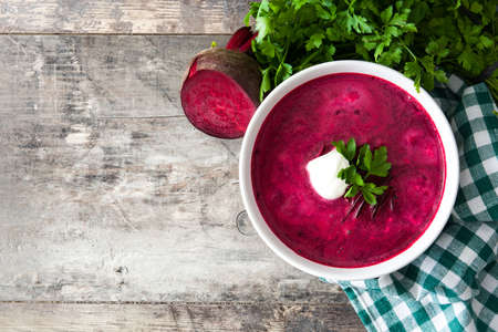 Beet soup in white bowl on wooden table. Top view Copyspace