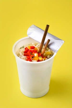 Take away noodles with vegetables on yellow background Banco de Imagens