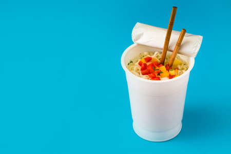 Take away noodles with vegetables on blue background. Copyspace