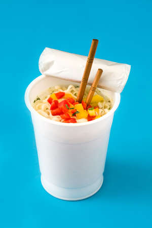 Take away noodles with vegetables on blue background