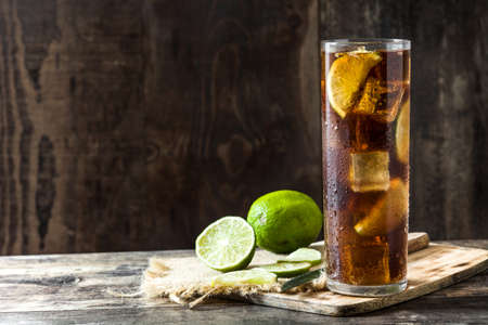 Cuba libre. Cocktail with rum, lime and ice on wooden table. Copyspace Stock fotó
