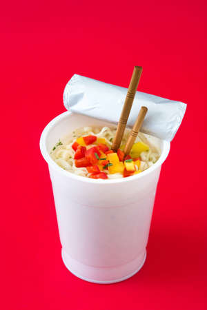 Take away noodles with vegetables on red background. Banco de Imagens