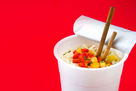 Take away noodles with vegetables on red background. Copyspace