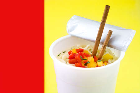 Take away noodles with vegetables on red and yellow background. Copyspace