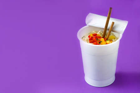 Take away noodles with vegetables on violet background. Copyspace
