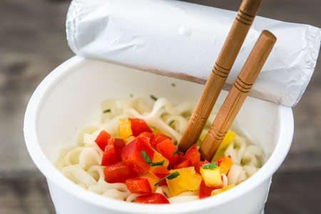 Take away noodles with vegetables on wooden table. Close up Banco de Imagens
