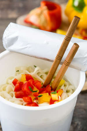 Take away noodles with vegetables on wooden table.