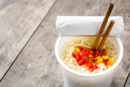 Take away noodles with vegetables on wooden table.Copyspace