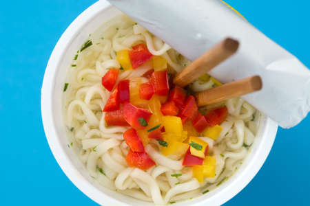 Take away noodles with vegetables on blue background. Top view