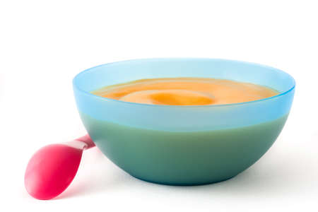 Baby food: blue bowl with fruit puree isolated on white background Stockfoto