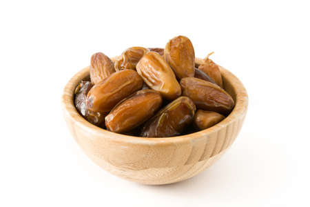 Dates food in wooden bowl isolated on white background