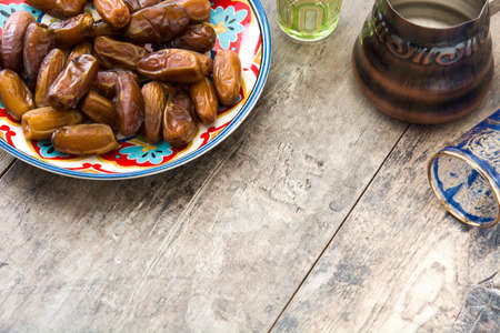 dates food in wooden bowl on wooden table. Copyspace