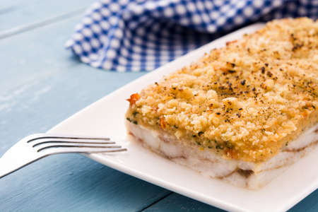 White fish casserole with cheese on blue wooden background.
