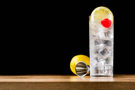 Classic Tom Collins cocktail on wooden table and black background. Copyspace