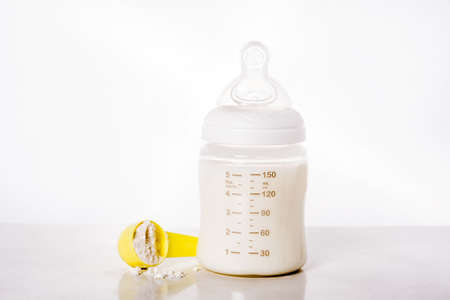 Baby bottle and milk on white background.