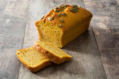 Homemade pumpkin bread on wooden table.