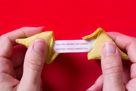 Biscotto della fortuna con messaggio su carta su sfondo rosso