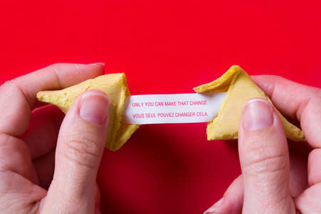 Fortune cookie with message on paper on red background