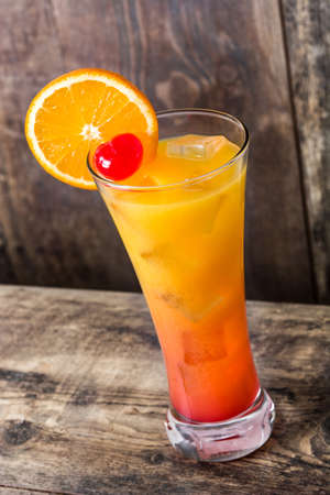 Tequila sunrise cocktail in glass on wooden table