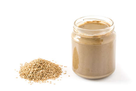 Tahini and sesame seeds isolated on white background