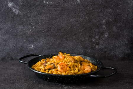 Fideua spagnola tradizionale. Paella di pasta su pietra nera. Copyspace