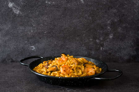Traditional Spanish fideua. Noodle paella on black stone. Copyspace
