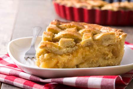 Homemade apple pie slice on wooden table
