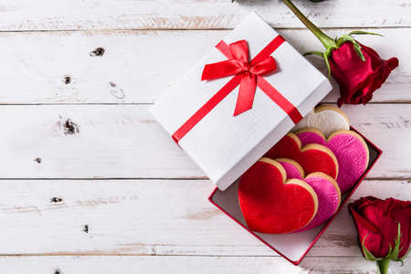 Heart-shaped cookies in gift box for Valentines Day on white wooden table. Top view. Copyspace