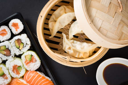 Dumplings or gyoza served in traditional steamer and sushi on black background. Flat lay top-down composition