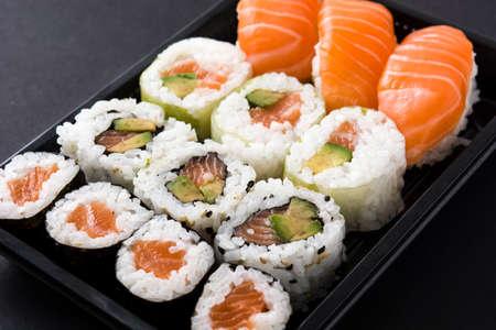 sushi pack with nigiri and maki on black background Imagens