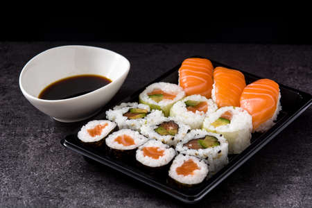 sushi assortment on black tray and soy sauce