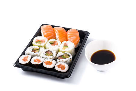 sushi assortment on black tray and soy sauce isolated on white background