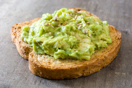 Toasted breads with avocado and sesame seeds on wooden table