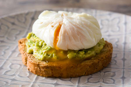 Close up avocado toast with poached egg on wooden table